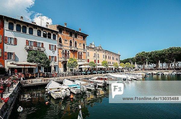 Boats on marina with tourists at cafes and restaurants at Desenzano del Garda  Lake Garda  Lombardy  Italian Lakes  Italy