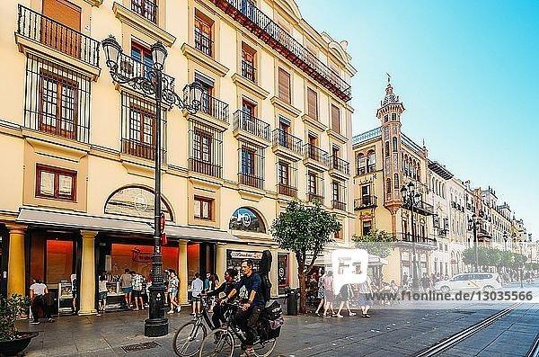 Pedestrians and cyclists on Avenida de la Constitucion in the historic centre of Seville  Andalusia  Spain