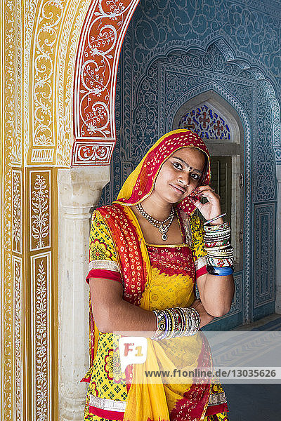 Lady wearing a colourful sari in ornate passageway  Samode Palace  Jaipur  Rajasthan  India