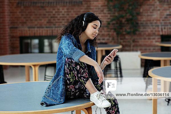 Teenager-Mädchen liest Textnachrichten auf Handy in der Schule