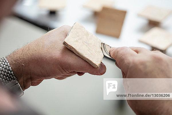 Zimmermann schleift Holzquadrat mit Schleifpapier