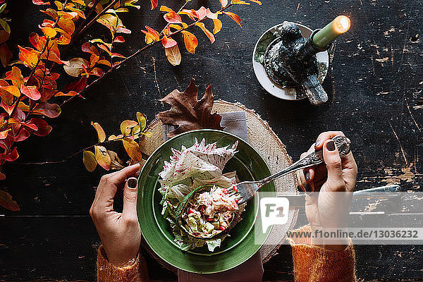 Woman eating fresh salad at vintage table  overhead view of hands