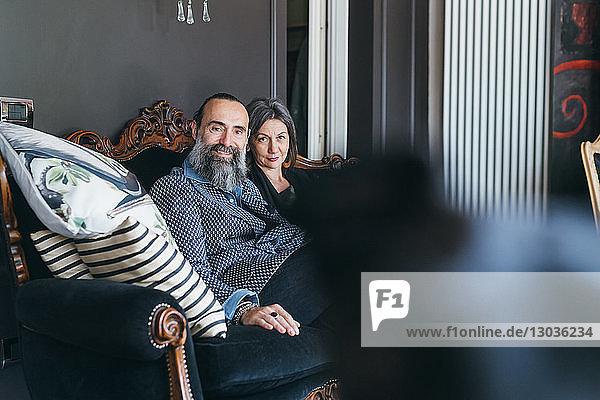 Paar auf dem Sofa  das in die Kamera schaut