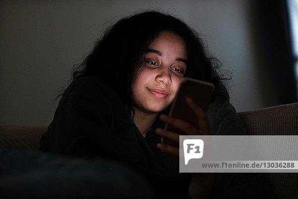 Teenager-Mädchen sitzt im Dunkeln auf dem Sofa und liest Textnachrichten
