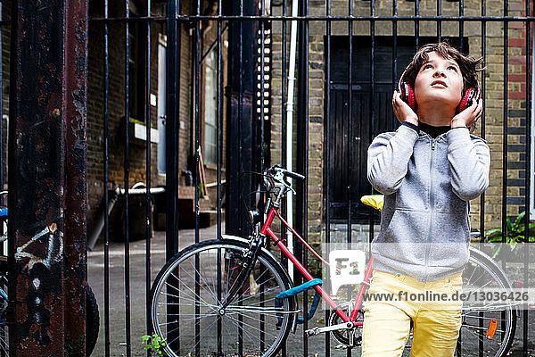 Junge  der mit Kopfhörern Musik hört  Fahrrad im Hintergrund
