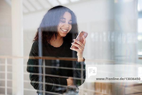 Teenager-Mädchen liest Textnachricht auf Handy an Glaswand