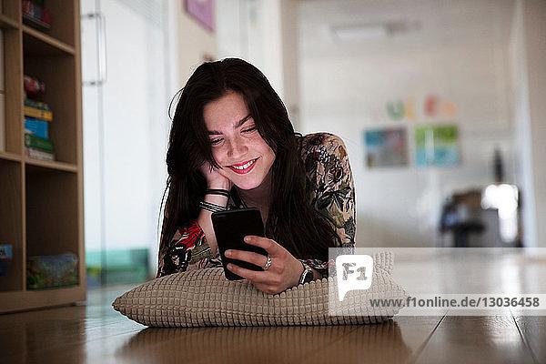 Teenager-Mädchen liegt auf einem Kissen auf dem Boden und liest eine Textnachricht