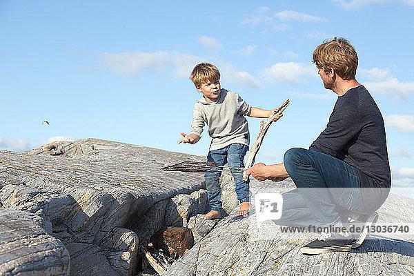 Junge und Vater bereiten ein Lagerfeuer auf dem Einlassfelsen vor  Aure  More og Romsdal  Norwegen