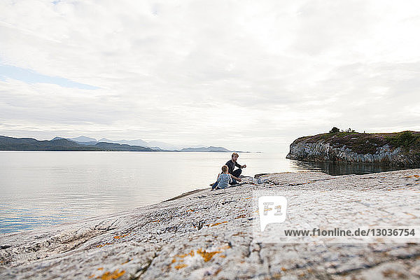 Boy and father eating food on inlet rock  Aure  More og Romsdal  Norway