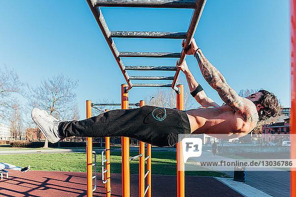Mann benutzt horizontale Leiter im Fitnessstudio im Freien