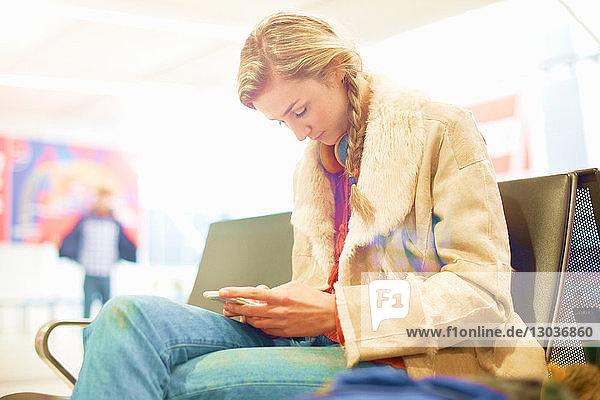 Young woman at airport  sitting  using smartphone