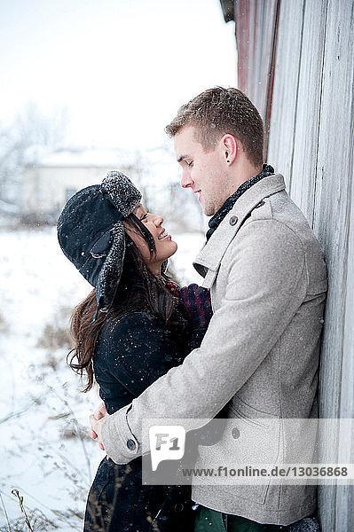 Junges Paar umarmt sich an Hütte im Schnee