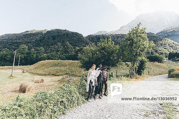 Junge erwachsene Wanderfreunde beim Daumenklauen auf ländlichem Feldweg  Primaluna  Trentino-Südtirol  Italien