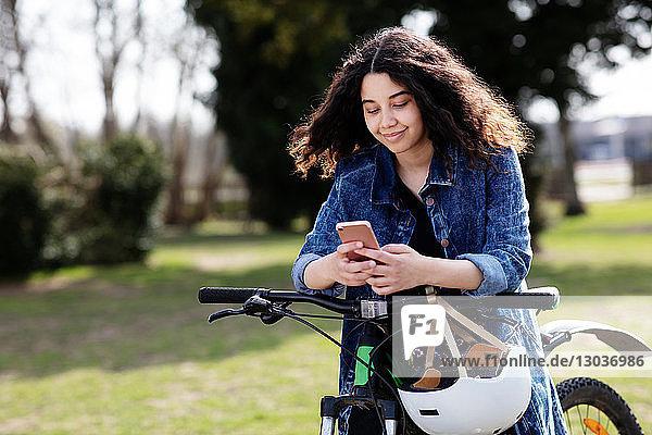 Teenager-Mädchen schreibt SMS auf dem Fahrrad