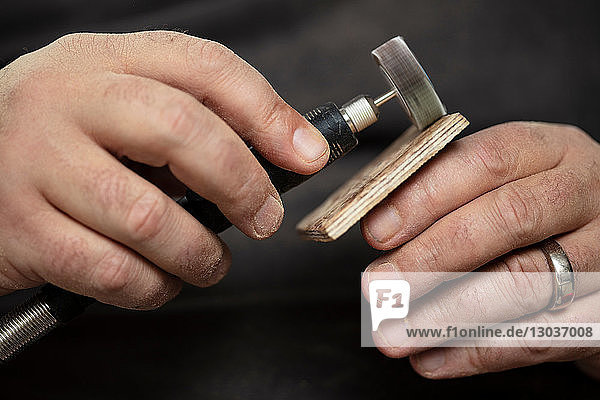 Carpenter sanding wood square with sanding tool