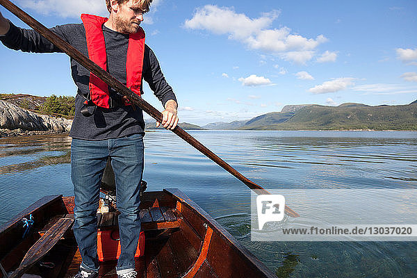 Mature man standing up to use oar in rowing boat  Aure  More og Romsdal  Norway