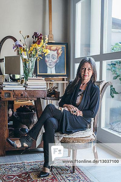 Frau sitzt auf Sessel am Fenster