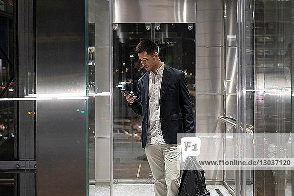 Junger Geschäftsmann nachts im Bürogebäude mit Blick auf Smartphone  Mailand  Italien