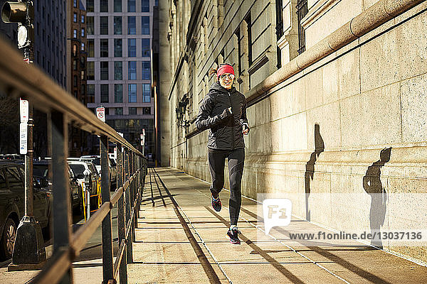 Full length shot of a single woman jogging in a city