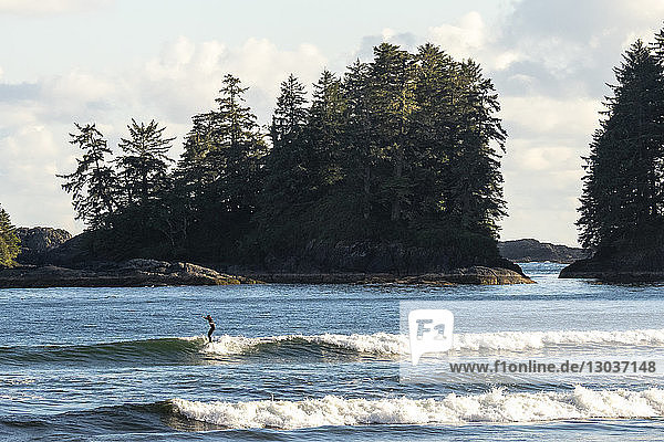 Distant view of a single surfer riding a wave in the sea  Florencia bay  Pacific Rim Park  Tofino  British Columbia  Canada