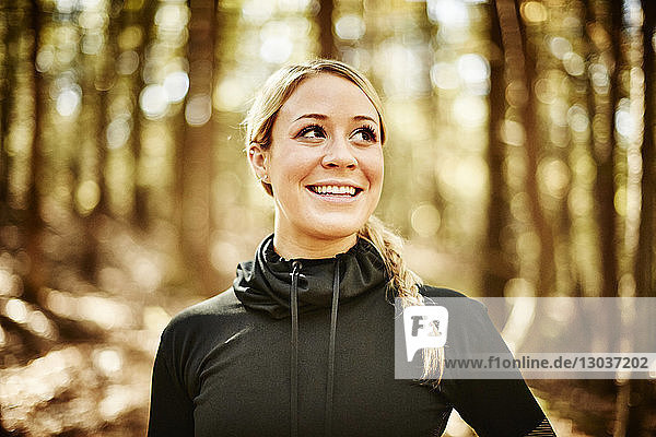 A head and shoulders portrait of a young blonde woman in sportswear in a forest