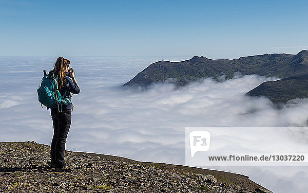 Full length shot of a female hiker taking picture of view of mountains rising above fog †Borgafjordur†Eystri  Iceland