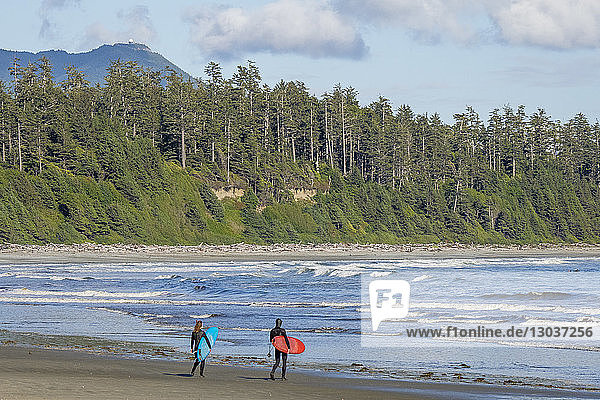 Two surfers in thick wetsuits prepare to enter the water at Florencia Bay in Pacific Rim Park in Tofino  British Columbia  Canada