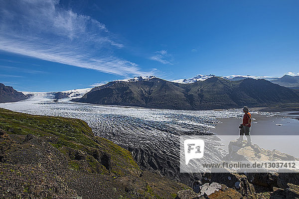 View of an adventurous male hiker looking at view of the Skaftafellsjokull glacier  Vatnajokull National Park  Iceland