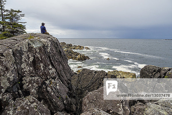View of a lone man sitting on a rock formation on seashore  Hot Springs Cove †Tofino  British Columbia  Canada