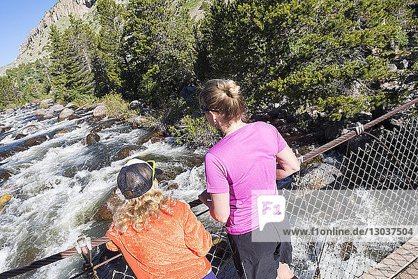 Rear view shot of a mother and daughter standing on a rope bridge over Popo Agie River  Sinks Canyon State Park  Lander  Wyoming  US