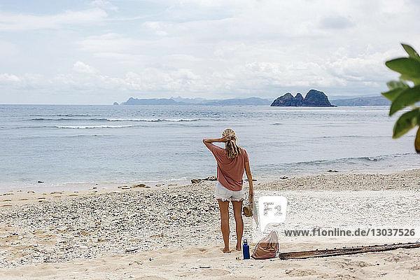 Rear view shot of single woman standing on beach  Kuta  Lombok  Indonesia