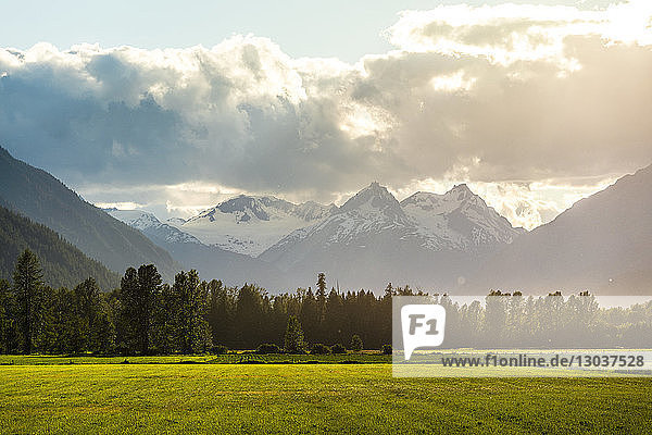 A field in the Pemberton Valley sits underneath Plinth Peak late summer light shines down through the clouds. Pemberton Valley nicknamed Spud Valley is a important agricultural community famous for producing seed potatoes  Pemberton  British Columbia  Canada