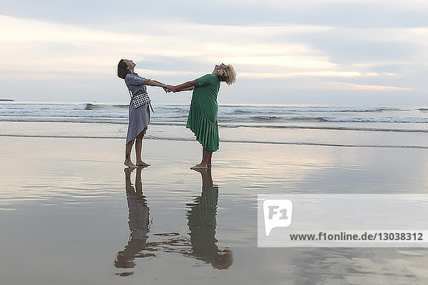 Full length of happy female friends holding hands while standing on shore at beach during sunset