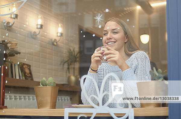 Smiling woman having coffee while sitting at table in cafe during Christmas seen through window
