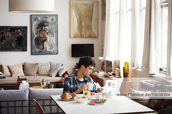 Junger Mann benutzt Laptop beim Kaffeetrinken zu Hause