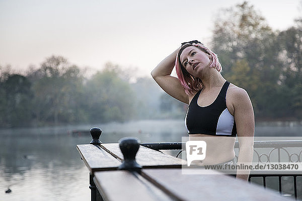 Woman stretching neck while standing by lake at park