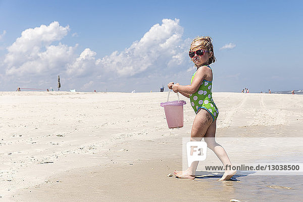 Full length of girl wearing one piece swimsuit and sunglasses while carrying bucket at beach during sunny day