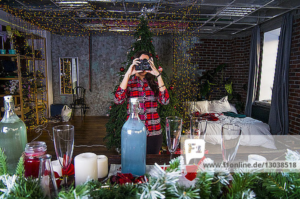 Woman photographing Christmas decoration on table