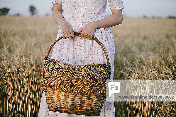 Midsection of woman holding wicker basket while standing amidst crops