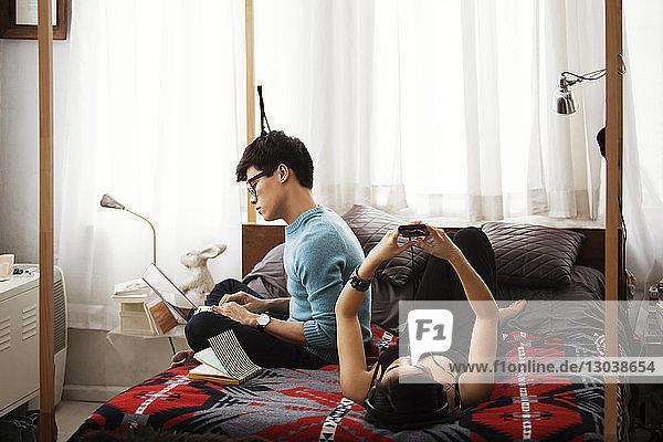 Ehepaar nutzt Laptop und Smartphone  während es sich im Schlafzimmer entspannt