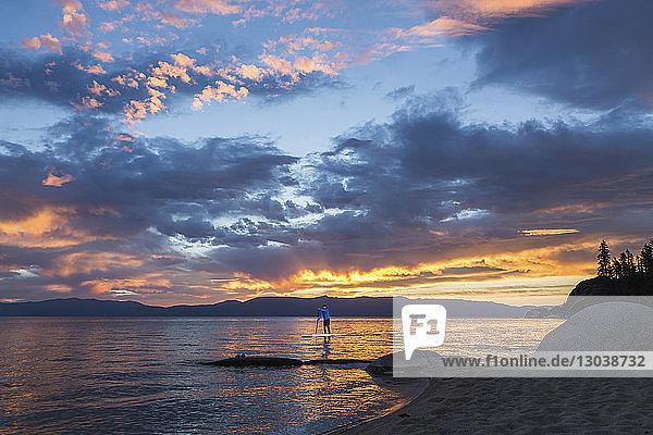 Mann paddelt auf See gegen bewölkten Himmel
