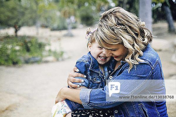 Glückliche Mutter umarmt Tochter  während sie im Hinterhof sitzt
