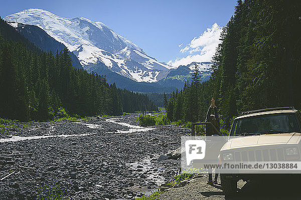 Rear view of hiker stretching arms while standing by Sports Utility Vehicle against mountains at Mount Rainer National Park