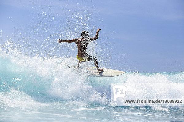 Rear view of man surfboarding on waves in sea against sky