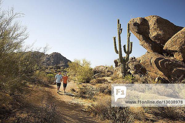 Paar auf unbefestigter Straße in der Wüste bei klarem Himmel