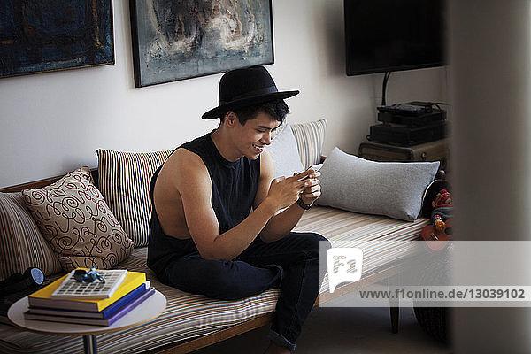 Glücklicher Mann mit Smartphone zu Hause auf dem Sofa sitzend
