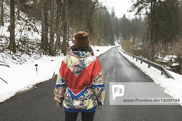 Rückansicht einer Frau in warmer Kleidung  die im Winter auf einer Landstraße zwischen Bäumen im Wald steht