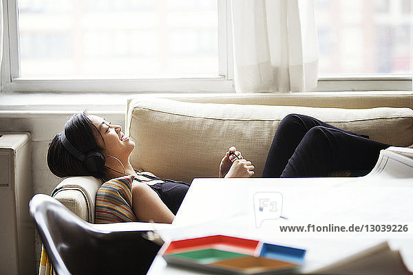 Seitenansicht einer glücklichen Frau  die Musik hört  während sie zu Hause auf dem Sofa liegt