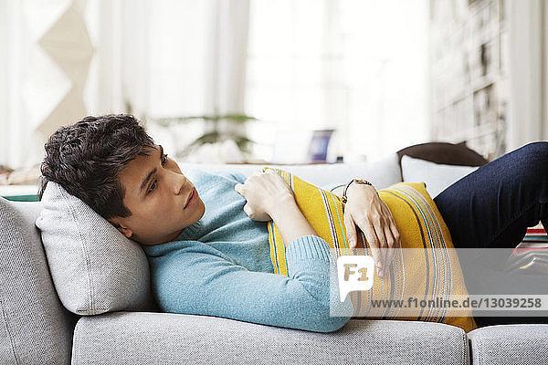 Nachdenklicher Mann hält Kissen  während er zu Hause auf dem Sofa liegt