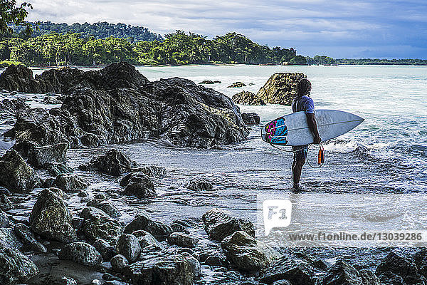 Surfer carrying surfboard while standing at beach